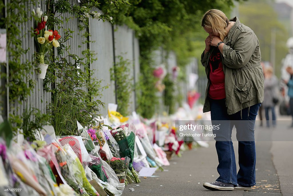 A woman views tributes to slain teacher Anne Maguire outside Corpus Christi Catholic College in Neville Road on on April 30, 2014 in Leeds, England. A fifteen year old male student has been arrested in connection with the death of teacher Ann Maguire, 61, who died from multiple stab wounds after the attack in her classroom at Corpus Christi Catholic College.