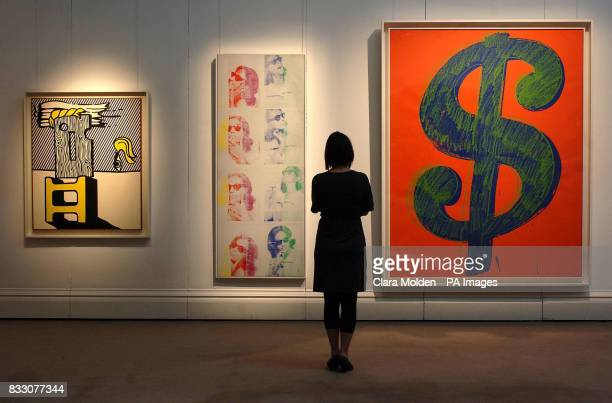 A woman views works by Roy Lichtenstein and Andy Warhol at Sothebys auction house in London