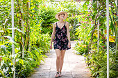 Beautiful woman enjoying beauty of tropical forest, walking on footpath. Surrounded by tropical nature.