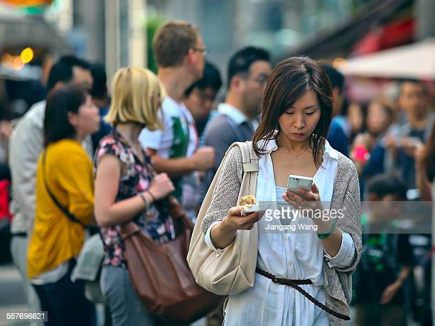 Woman visiting Tsukiji Outer Market watching on her smart phone