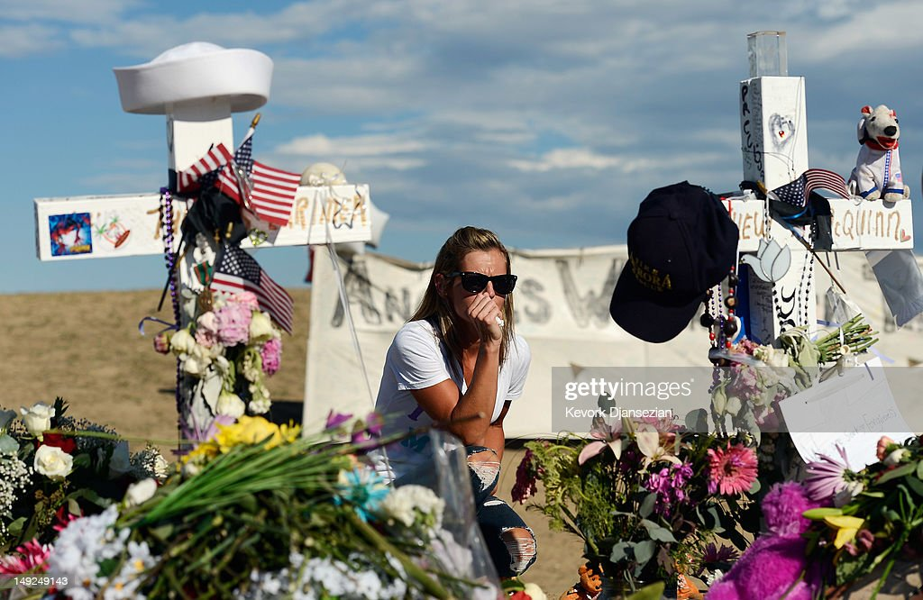 A woman visits the makeshift memorial for the 12 movie theater shooting victims built across the street from the Century 16 Theater July 25, 2012 in Aurora, Colorado. Twenty-four-year-old James Holmes is suspected of killing 12 and injuring 58 others on July 20 during a shooting rampage at a screening of 'The Dark Knight Rises' in Aurora, Colorado.