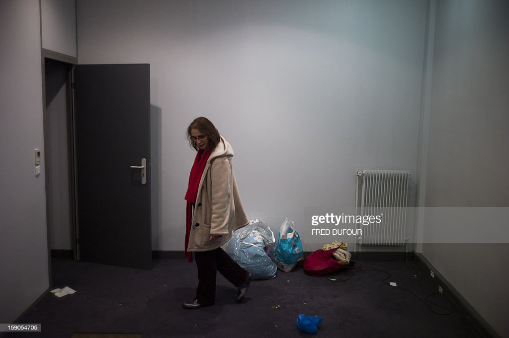 A woman visits the room she will occupy in a building requisitioned by French associations 'Jeudi Noir' ('Black Thursday') and 'Droit Au Logement', ('Right to Housing Association', DAL), on January 6 , 2013 in Paris. The building, situated in the 10th arrondissement of Paris is occupied since December 31, 2012.
