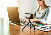 Woman vlogger looking using laptop computer and filming on video her life - New job trends concept - Girl sharing on internet social networks lifestyle contents - Focus on tripod camera - Warm filter