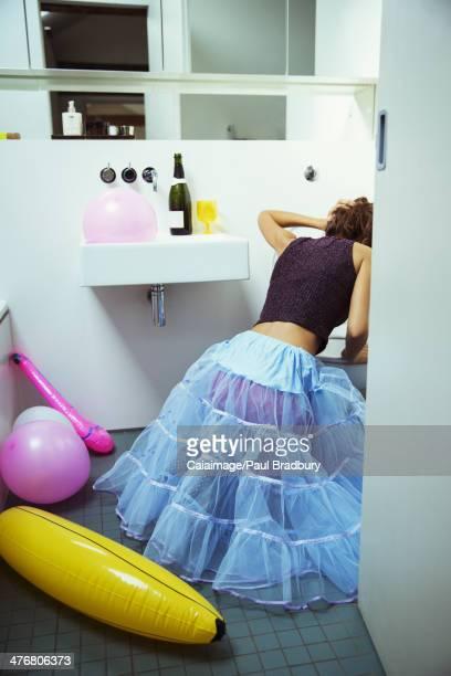 Frau in der Toilette auf party zum Erbrechen