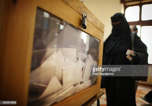 A woman voter stands next to a ballot box with a transparent side at a polling station at a girls school on November 28 2011 in Downtown Cairo Egypt...