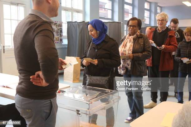 A woman votes in the first round of the Presidential race in the Belleville neighbourhood a mixed ethnic area in the 19th arrondissement on April 23...