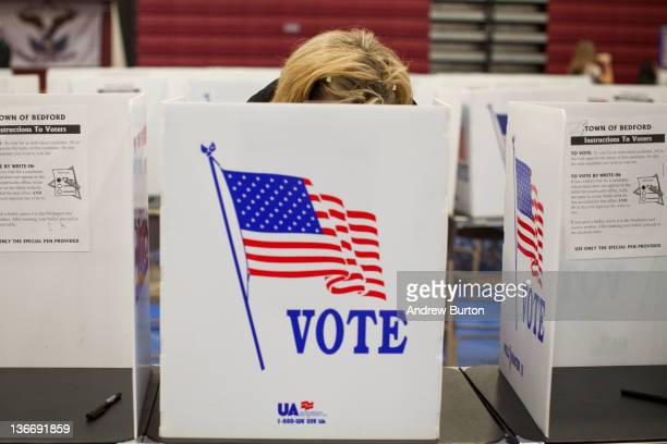 A woman votes in the New Hampshire primary at Bedford High School on January 10 2012 in Bedford New Hampshire Voters in New Hampshire headed to the...