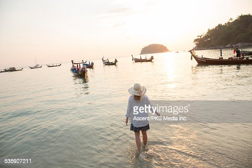 Woman wades in sea shallows, looks out to boats : Stock Photo