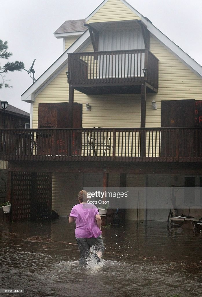 A woman wades toward her flooded home during Hurricane Irene on August 27, 2011 in Kill Devil Hills, North Carolina. Hurricane Irene hit Dare County, which sits along the Outer Banks and includes the vacation towns of Nags Head, Kitty Hawk and Kill Devil Hills, as a category one hurricane around mid-day today causing wind damage and flooding.