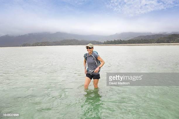 Woman wading across lagoon