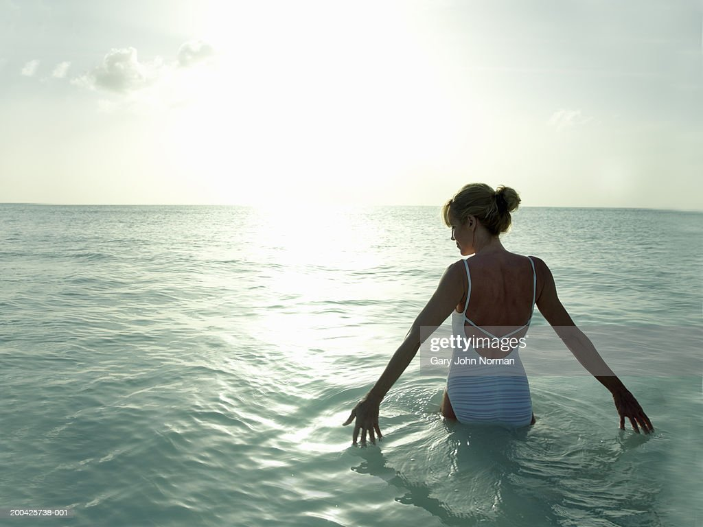 Woman wading in ocean, rear view : Stock Photo