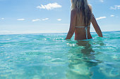 Woman wading in turquoise water on a tropical beach. She is wearing a white bikini and looks relaxed. Sunny weather, cropped image