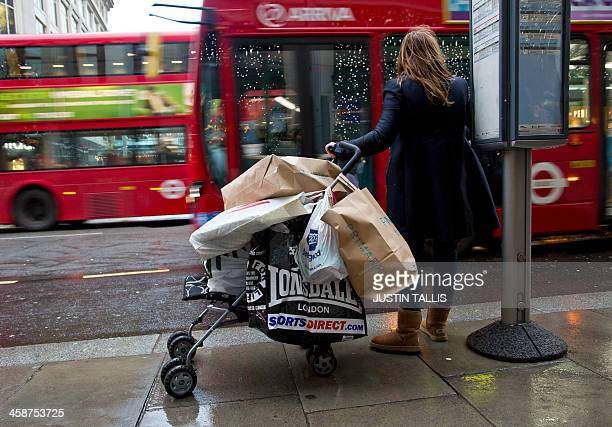 A woman waiting at a bus stop uses a push chair to carry all her shopping bags on Oxford Street in central London on December 21 2013 AFP...