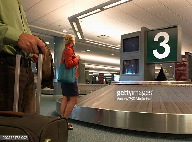 Woman waiting at baggage carousel in airport