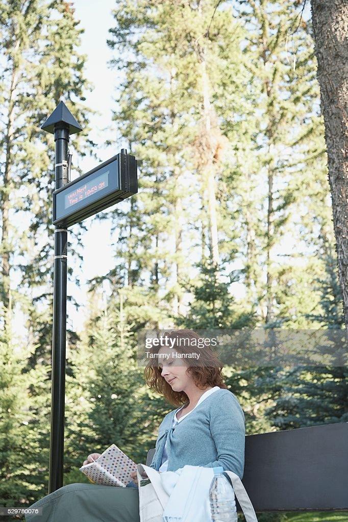 Woman waiting at bus stop : Foto de stock