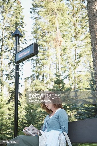 Woman waiting at bus stop : Bildbanksbilder