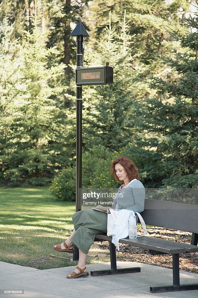 Woman waiting at bus stop : Stock Photo