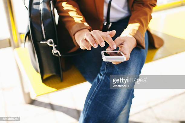 Woman waiting at the bus stop using smartphone