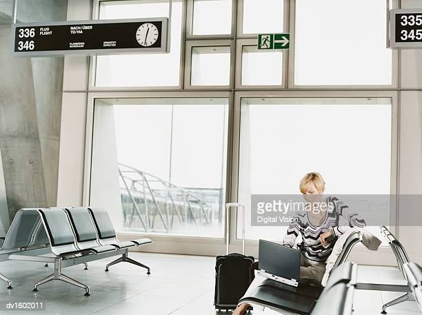A Woman Waiting in an Aiport Departure Lounge, Using a Laptop Computer