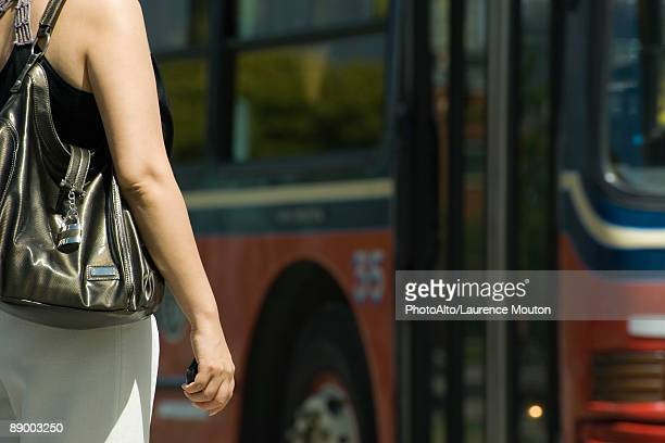 Woman waiting in front of bus, cropped
