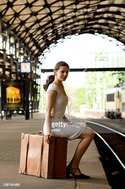 Femme attendant à la gare ferroviaire de bagages