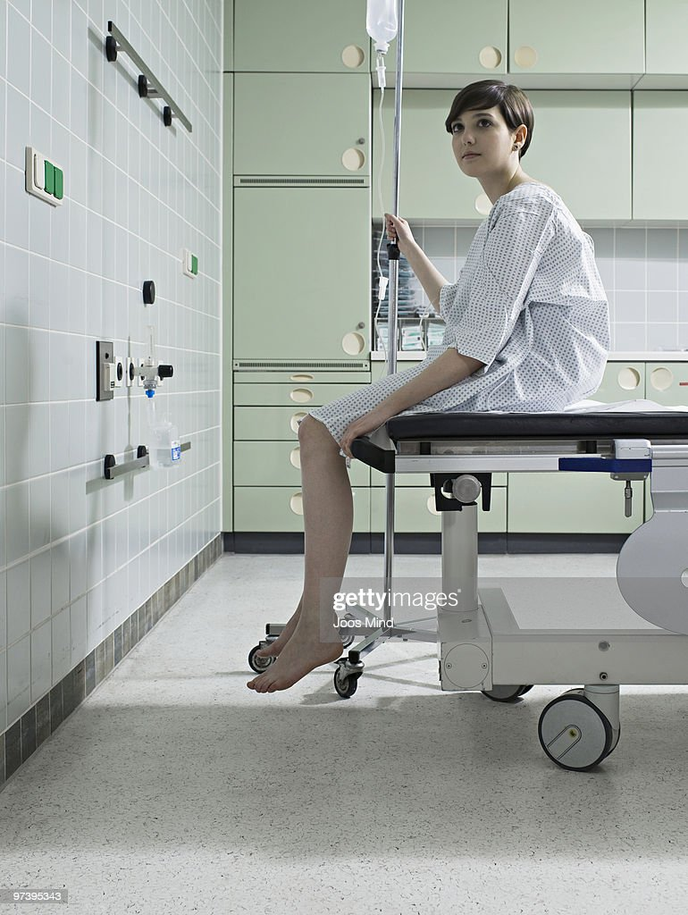 woman waiting on examination table in hospital : Stock Photo