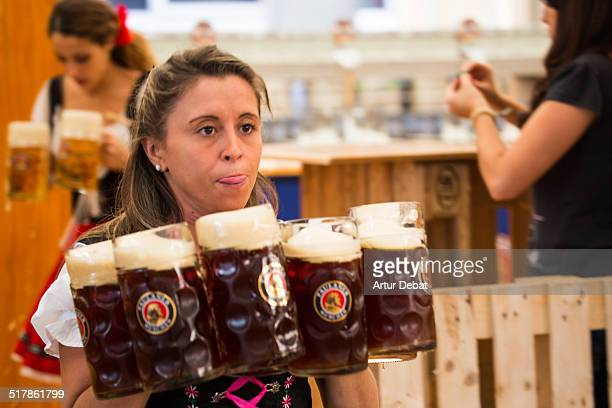 Woman waitress wearing the tradition Bavarian dress with beers in the Oktoberfest of Barcelona Catalonia Europe