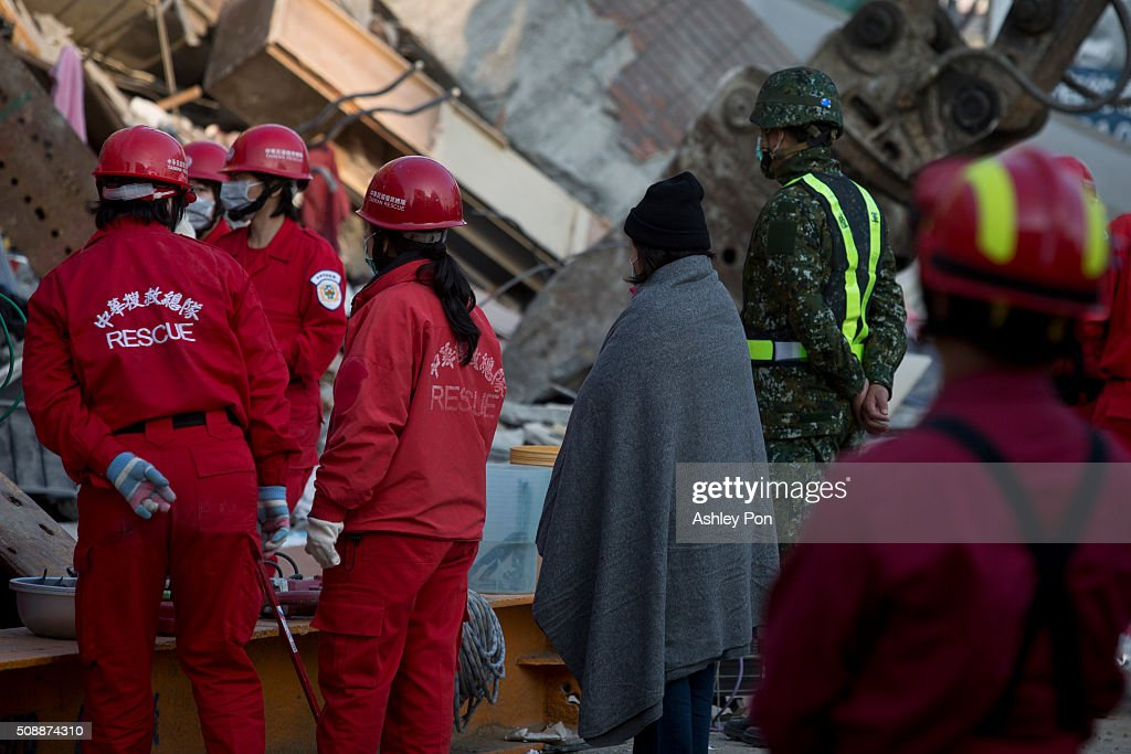 A woman waits at the site of a collapsed building as the rescue operation contines on February 7, 2016 in Tainan, Taiwan. A magnitude 6.4 earthquake hit southern Taiwan early Saturday, toppling several buildings, killing at least fourteen people, and leaving over one hundred missing in Tainan.