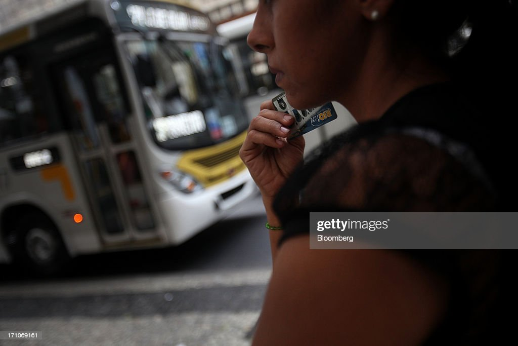 A woman waits for a bus on the Presidente Getulio Vargas Avenue in Rio de Janeiro, Brazil, on Friday, June 21, 2013. Brazils swelling street rebellion claimed its second fatality in the largest and most violent protests yet, as 1 million demonstrators rallied for better public services and an end to corruption. Photographer: Dado Galdieri/Bloomberg via Getty Images