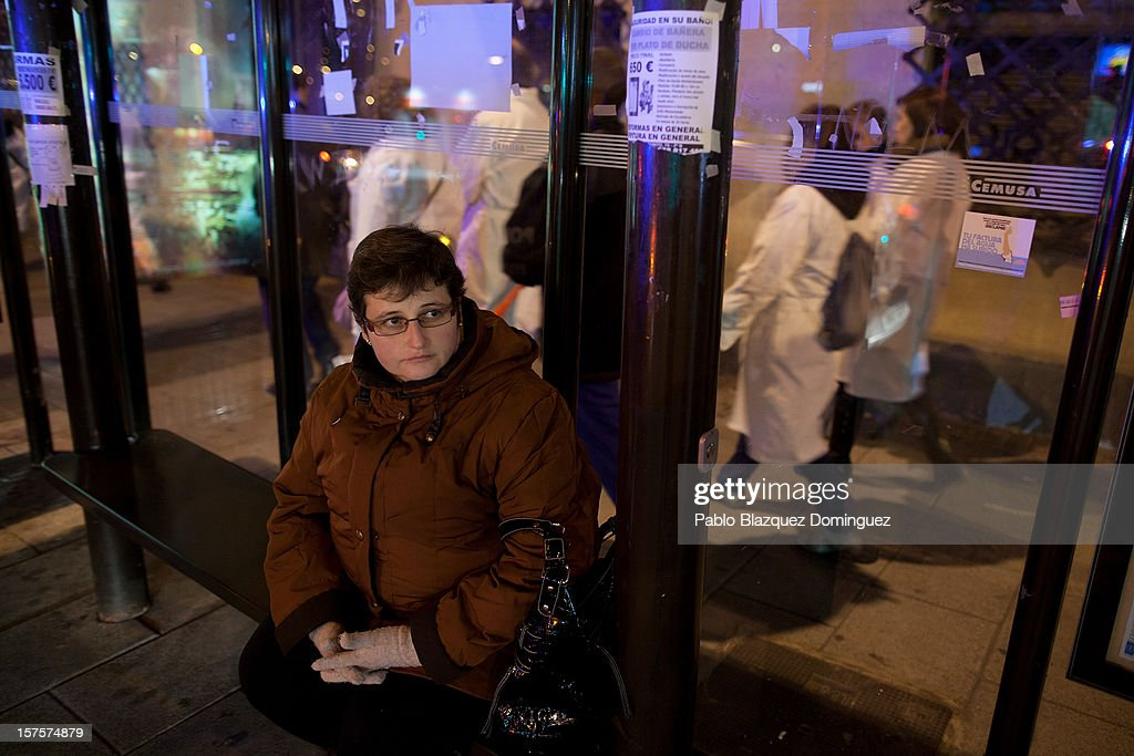 A woman waits for a bus while a health workers demonstration walks past near Puente de Toledo on December 4, 2012 in Madrid, Spain. All trade unions called for the second 48 hours health workers' general strike in Madrid region, after Regional Government announced severe cuts and privatization of Medical Centers.