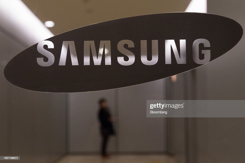A woman waits for an elevator behind a Samsung Electronics Co. logo displayed at the company's Seocho office building in Seoul, South Korea, on Friday, March 15, 2013. Samsung Electronics's President of visual display Yoon Boo Keun and President of mobile communications J.K. Shin were appointed as co-chief executive officers following the company's shareholder meeting today, joining Vice Chairman Kwon Oh Hyun, who will also retain his position as co-CEO. Photographer: SeongJoon Cho/Bloomberg via Getty Images