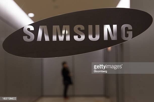 A woman waits for an elevator behind a Samsung Electronics Co logo displayed at the company's Seocho office building in Seoul South Korea on Friday...