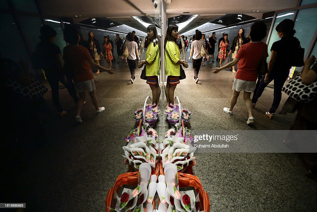 A woman waits for customers during Valentine's Day in an underpass along Orchard Road on 14 February, 2013 in Singapore. Valentine's Day is a time to celebrate love, romance and friendship and is celebrated worldwide annually in different ways on February 14.