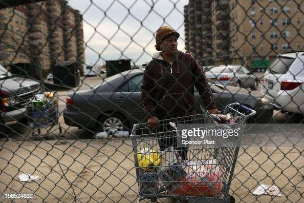 A woman waits for discarded food from a flooded grocery store in the heavily damaged Rockaway neighborhood where a large section of the iconic...