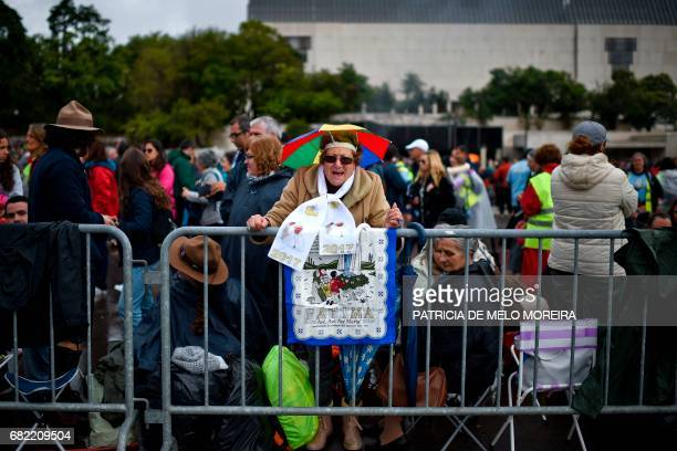 A woman waits for the arrival of Pope Francis in Fatima central Portugal on May 12 2017 Two of the three child shepherds who reported apparitions of...