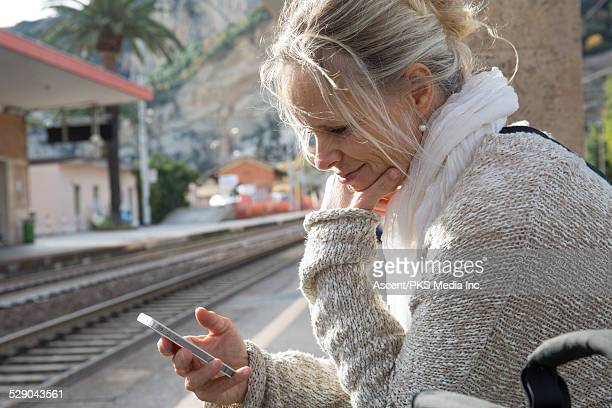 Woman waits for train at station, uses smart phone