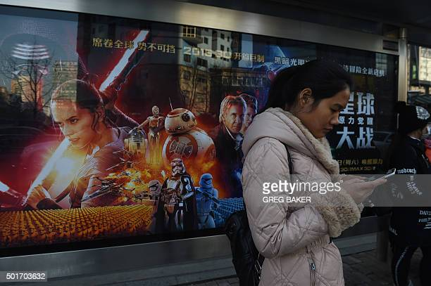 A woman waits in front of a poster for 'Star Wars The Force Awakens' at a bus stop in Beijing on December 17 2015 The movie opens in China on January...