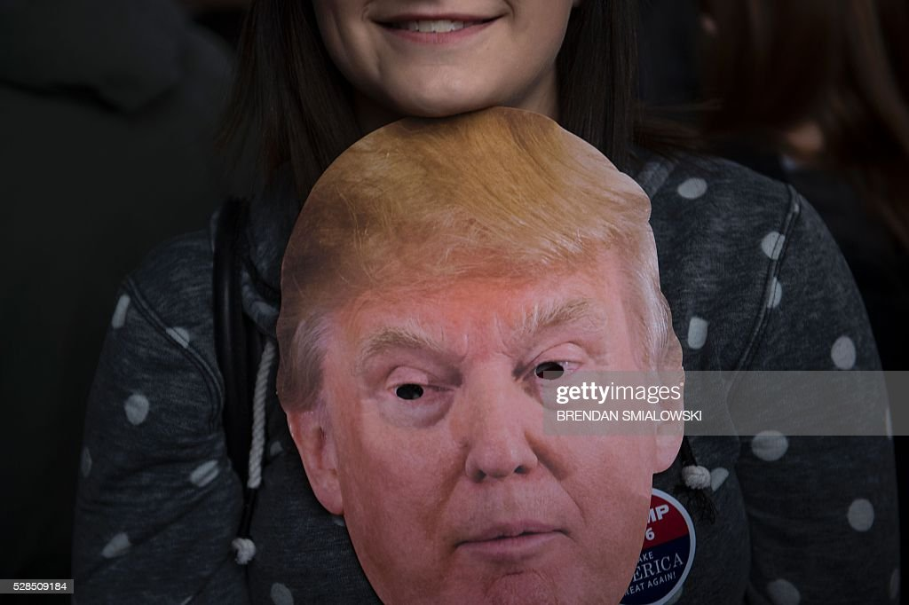 A woman waits in line with a Donald Trump mask before a rally for Republican US Presidential hopeful Donald Trump in Charleston, West Virginia on May 5, 2016. It's the paradox of the 2016 US presidential elections: Hillary Clinton and Donald Trump are virtually assured of facing off against each other in November, and yet both are widely unpopular. / AFP / Brendan Smialowski