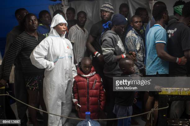A woman waits in line with her children as refugees and migrants are taken onboard the Migrant Offshore Aid Station Phoenix vessel after being...