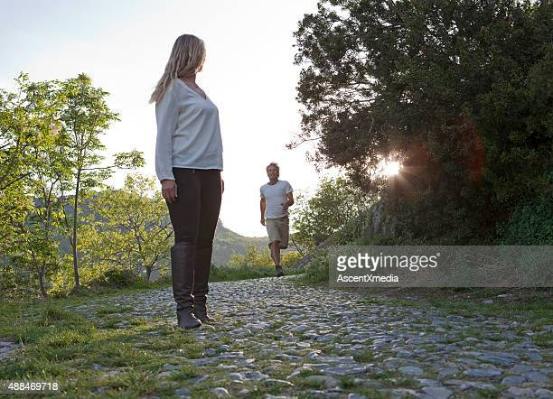 Woman waits on cobblestones while man catches up