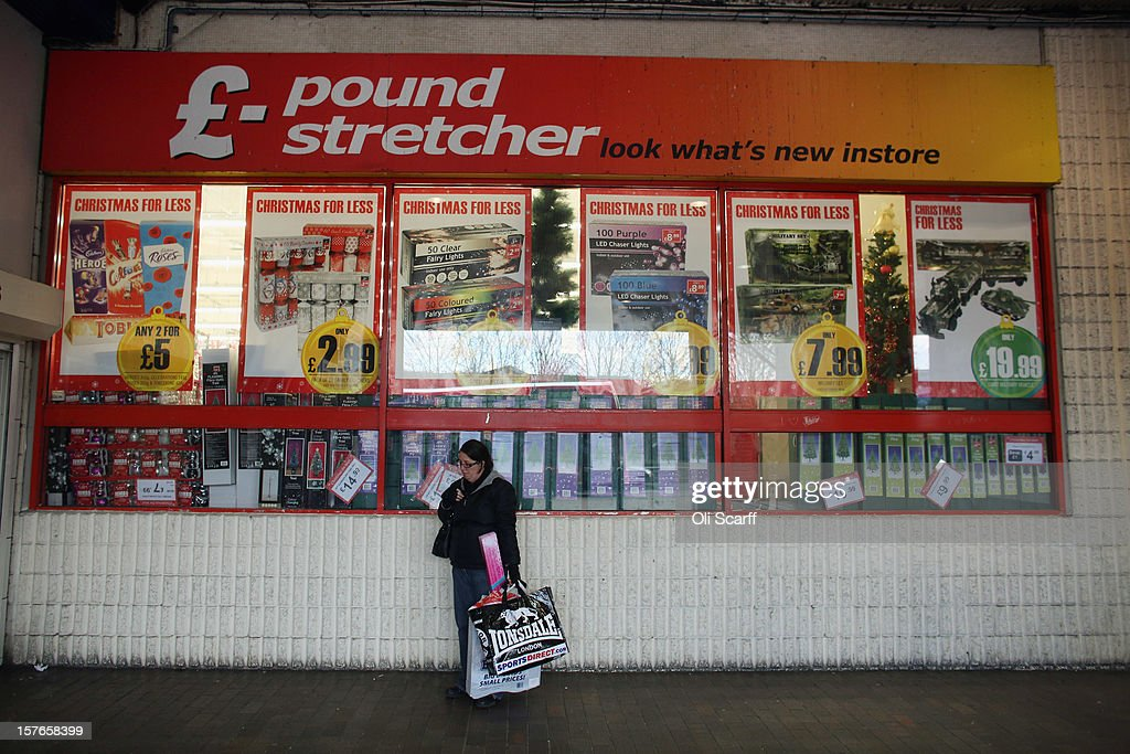 A woman waits outside a branch of Poundstretcher near Lewisham high street on December 5, 2012 in London, England. The Chancellor of the Exchequer George Osborne has stated that the United Kingdom's economy is still struggling during his autumn budget statement to Parliament.