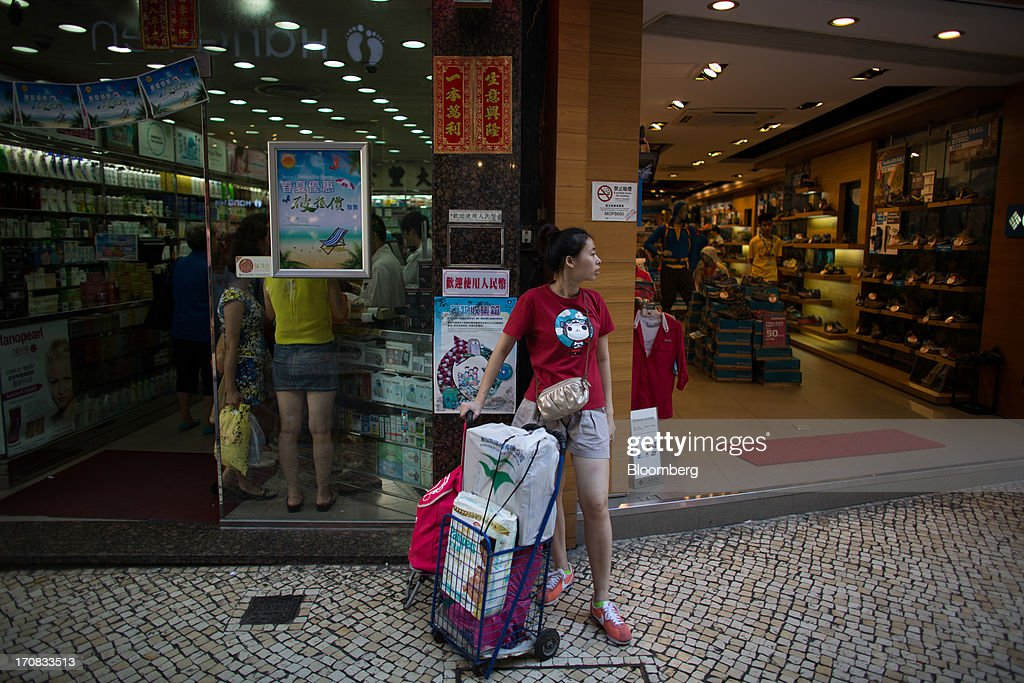 A woman waits outside stores with baggage in the city center of Macau, China, on Tuesday, June 18, 2013. Casino revenue in Macau, the only place in China where casino gambling is legal, rose 14 percent to a record of 304 billion patacas ($38 billion) in 2012. Photographer: Lam Yik Fei/Bloomberg via Getty Images