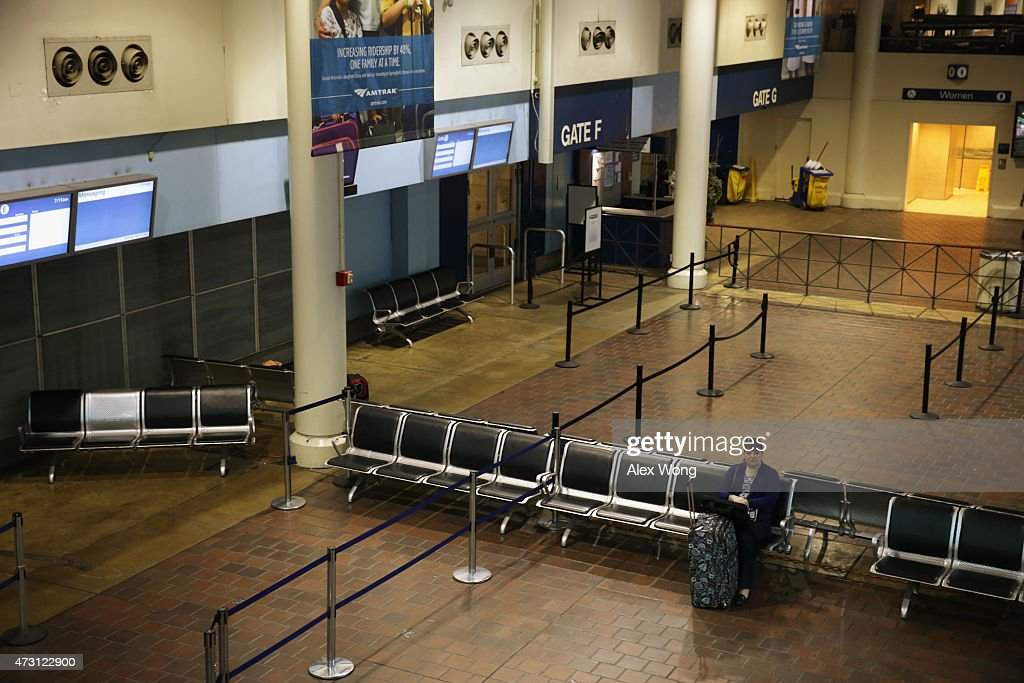 A woman waits to board her train at an almost empty boarding area at the Union Station on May 13 2015 in Washington DC Service has been interrupted...