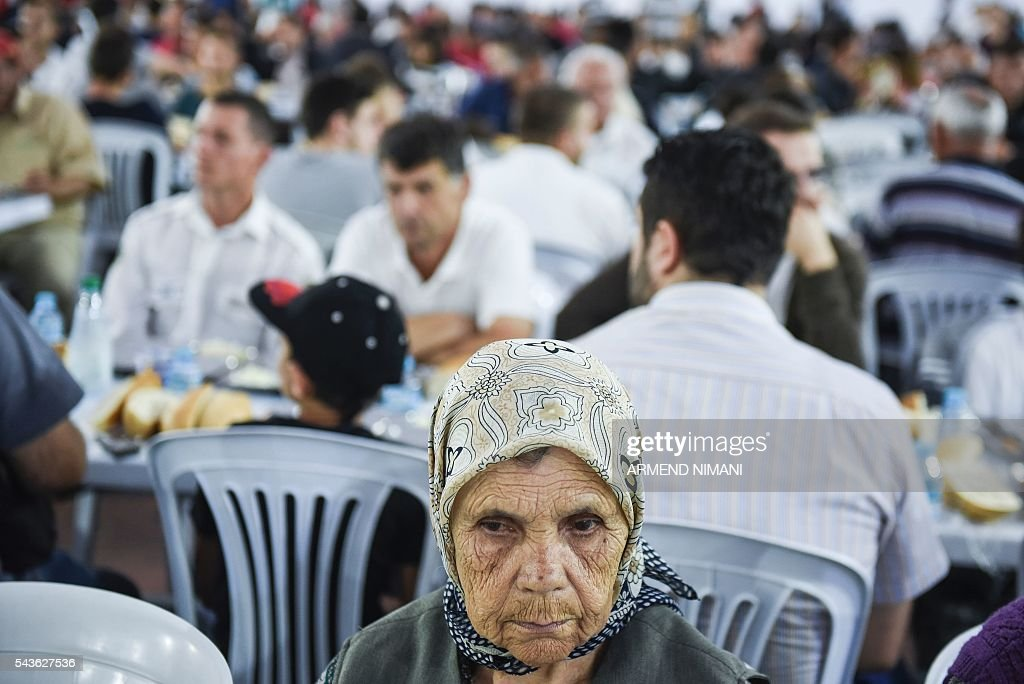 A woman waits to break the fast with a dinner distributed for free during the Muslim fasting month of Ramadan on June 29, 2016 in Pristina. Muslims fasting in the month of Ramadan must abstain from food, drink and sex from down to dusk, when they break the fast with meal known as iftar. / AFP / ARMEND