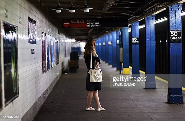 A woman waits to catch a train at a subway station in New York on October 28 2014 AFP PHOTO/Jewel Samad