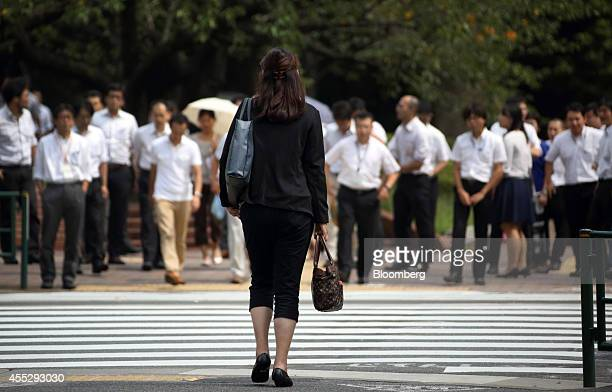 A woman waits to cross a road in the Kasumigaseki area of Tokyo Japan on Thursday Sept 11 2014 Losing women from the workforce in their 20s and 30s...