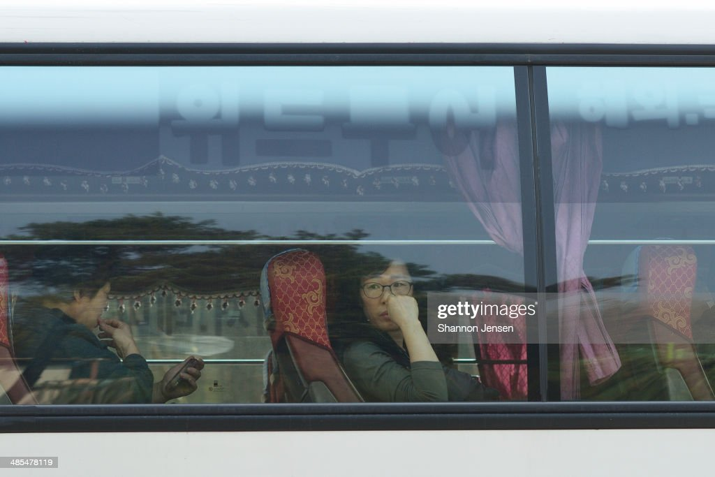 A woman waits to go to Jindo Island by bus from Danwon High School on April 18, 2014 in Ansan, South Korea. 325 students and 15 teachers of Danwon High School on a school trip were among the 477 passengers on board the ferry capsized off of Jindo Island in South Korea on April 16, 2014.