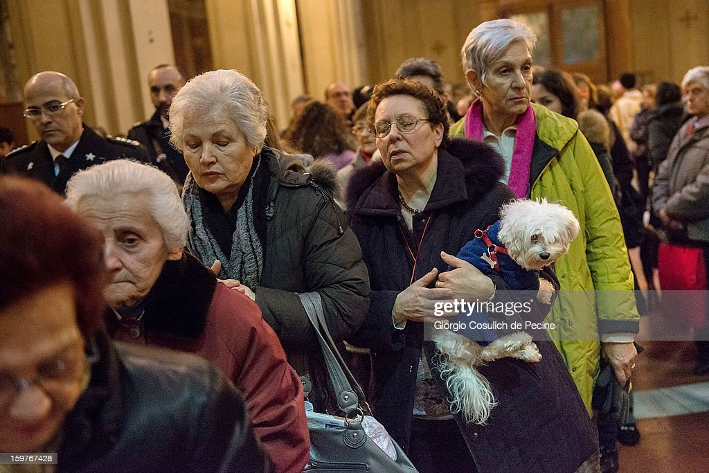 A woman waits to receive communion as she holds her dog during a traditional mass for the blessing of animals at the Sant'Eusebio church on January 20, 2013 in Rome, Italy. Every year during the feast of St. Anthony the Abbot animals are blessed in countries around the world.