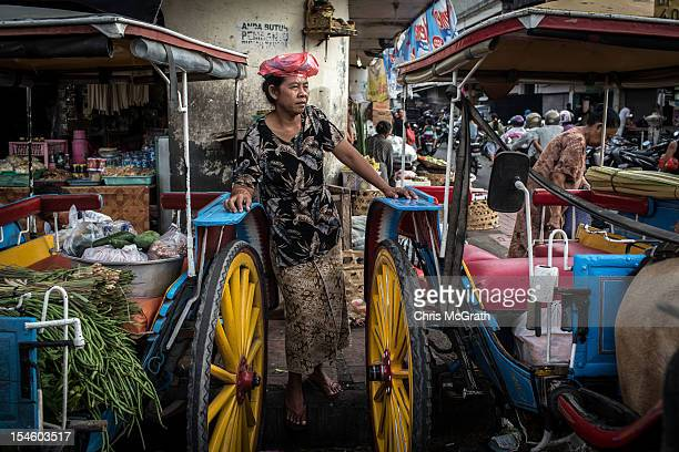 A woman waits to transport her produce in a Dokar at Badung market on October 14 2012 in Denpasar Bali Indonesia The Dokar is traditional local...
