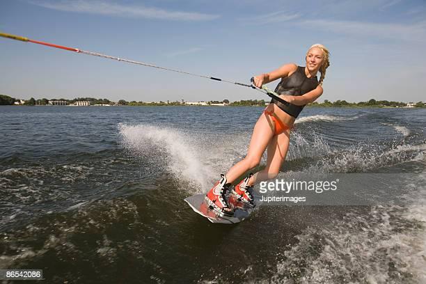 Woman wakeboarding on lake